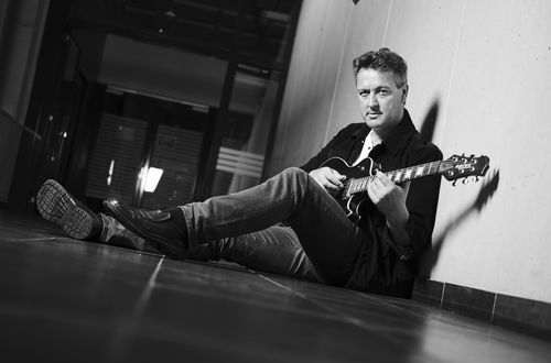 Portraitaufnahme in Schwarz-Weiss vom Musiker Phil Olavide, sitzend mit der Gitarre in der Hand